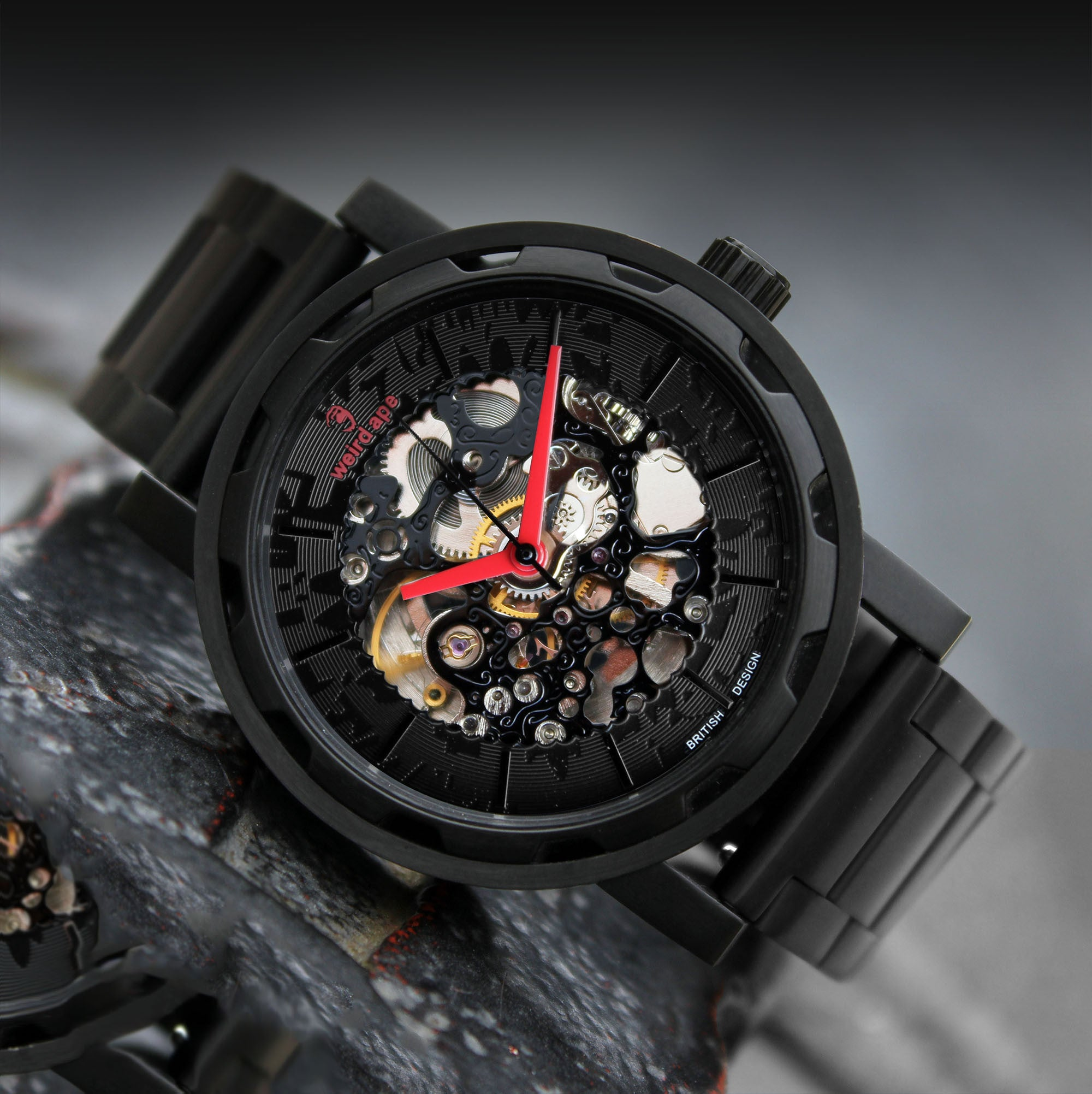 A picture of a black mechanical watch with red hands and a metal strap.