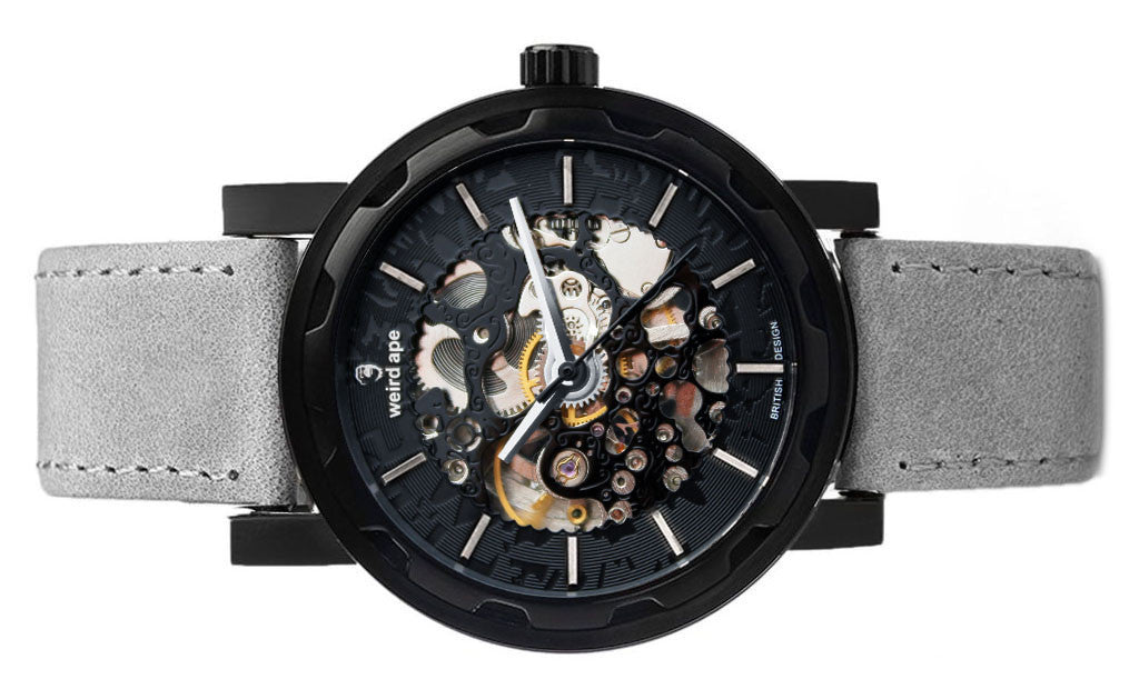 Black skeleton watch with grey suede strap.