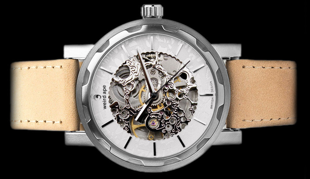 Silver mechanical watch with sandstone strap on its side.