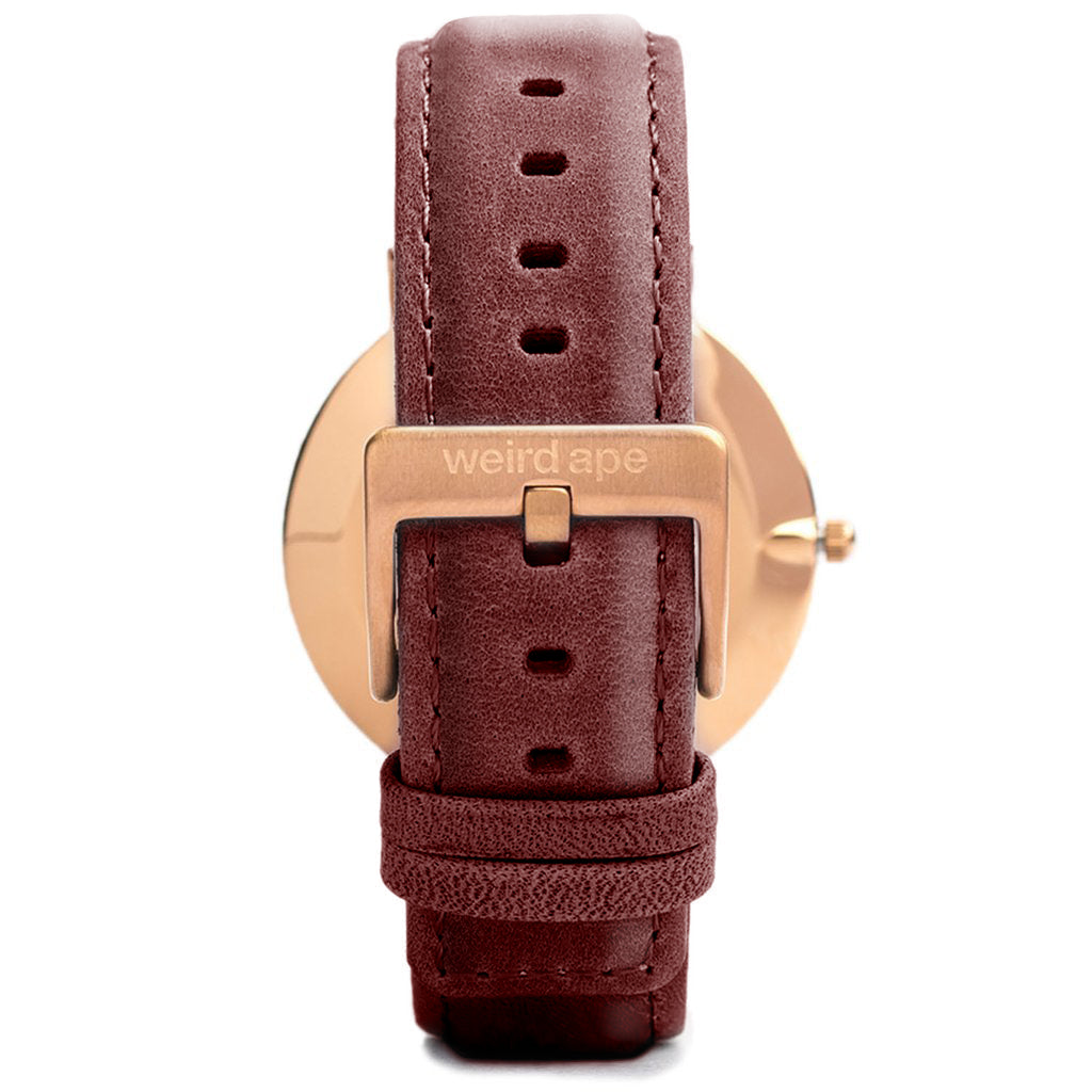 Back of a rose gold minimal watch with a burgundy strap called the Duke.