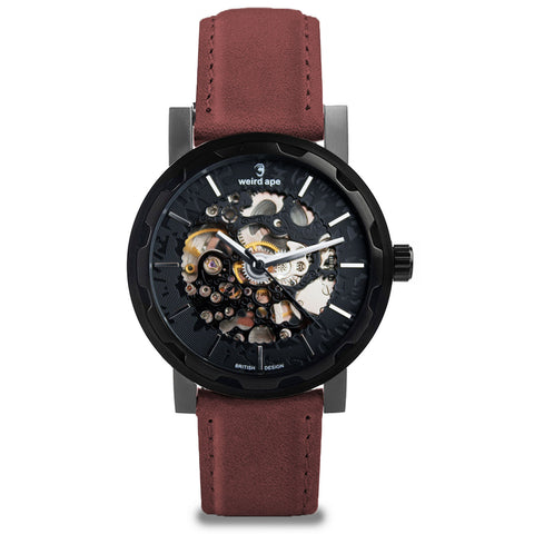 The Kolt black skeleton watch. A black mechanical watch with a burgundy leather strap.