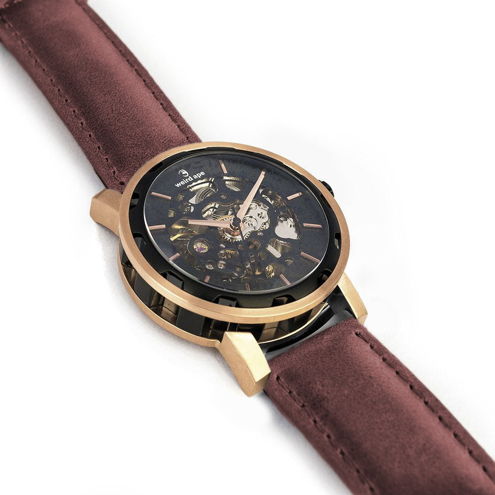 The Kolt rose gold skeleton watch. A rose gold mechanical watch with a burgundy leather strap.