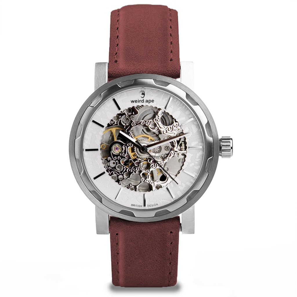 The Kolt silver skeleton watch. A silver mechanical watch with a burgundy leather strap.