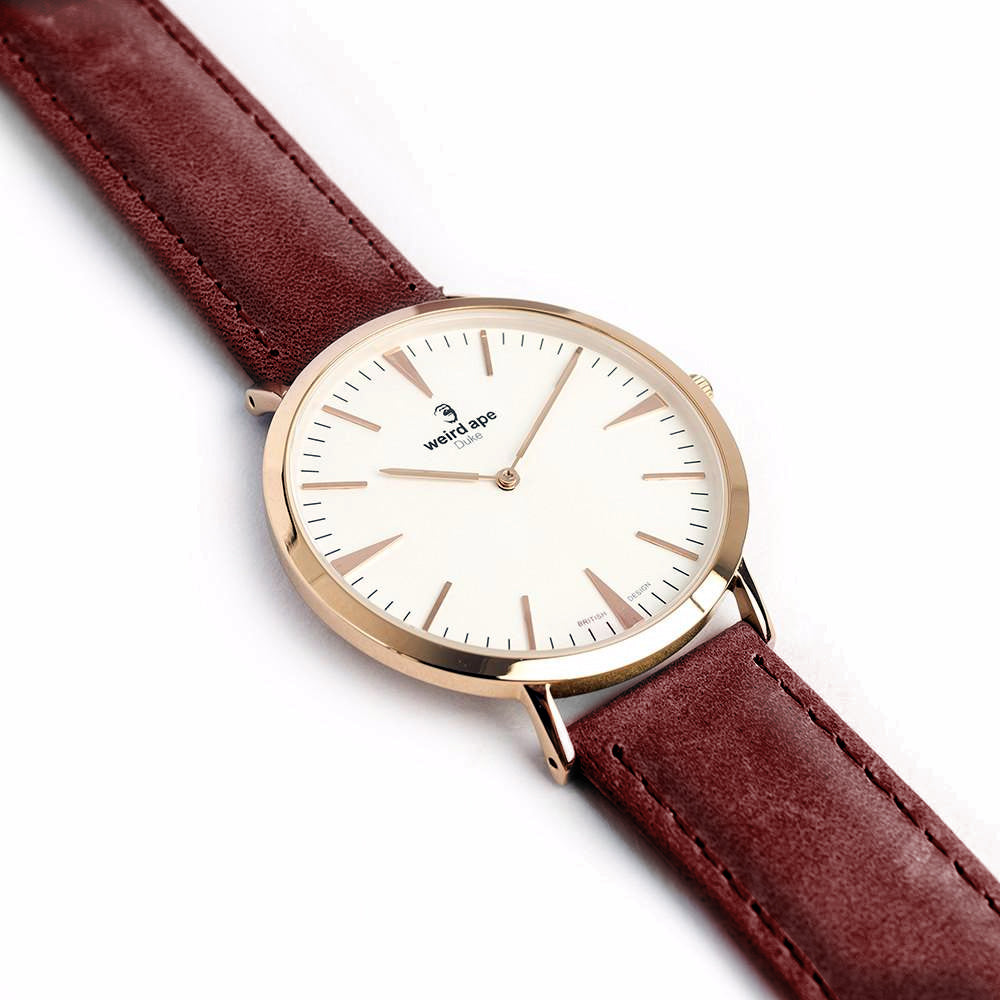 Side profile of a rose gold minimal watch with a burgundy strap called the Duke.