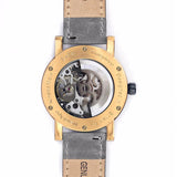Back of rose gold skeleton watch with grey leather strap showing the mechanical movement.