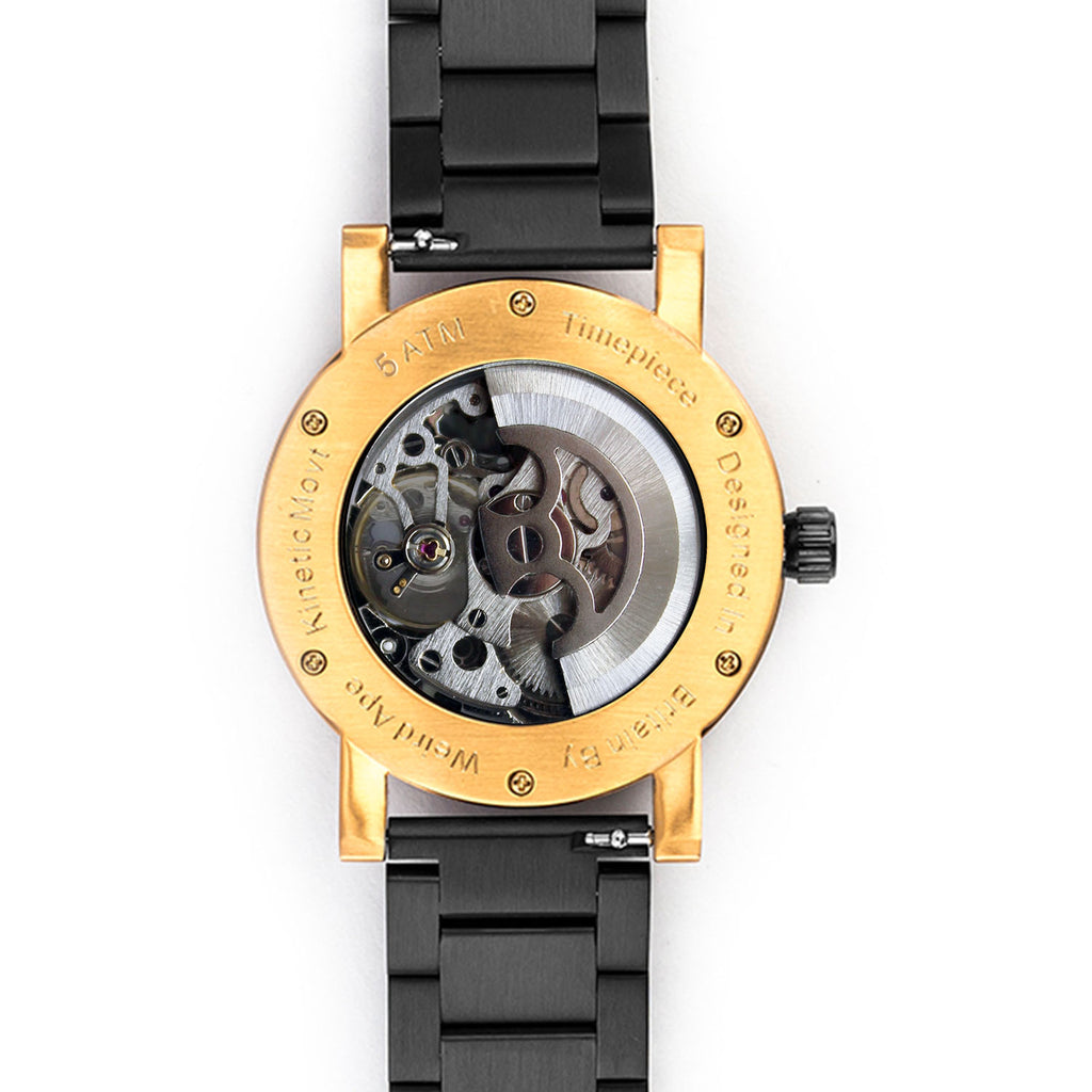 Back of rose gold skeleton watch with black strap showing the mechanical movement.
