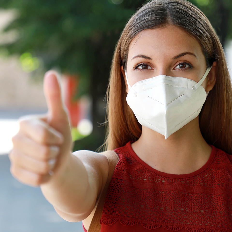 Woman wearing KN95 mask in public with thumbs up