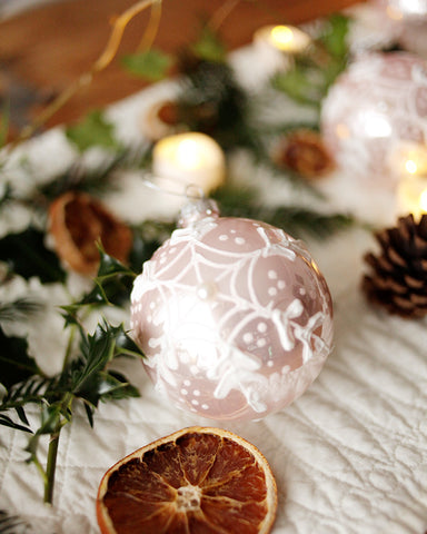 Pink ornate bauble decoration on table