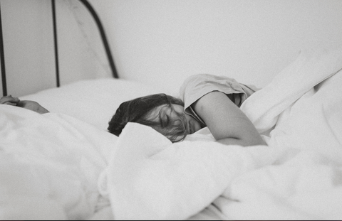 Sleeping female in duvet via Unsplash