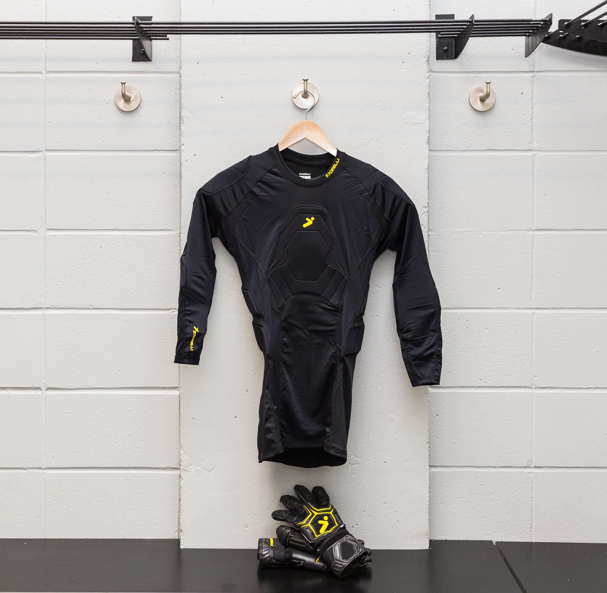 storelli sports 3/4 bodyshield goalkeeper top hanging from hangar in locker room