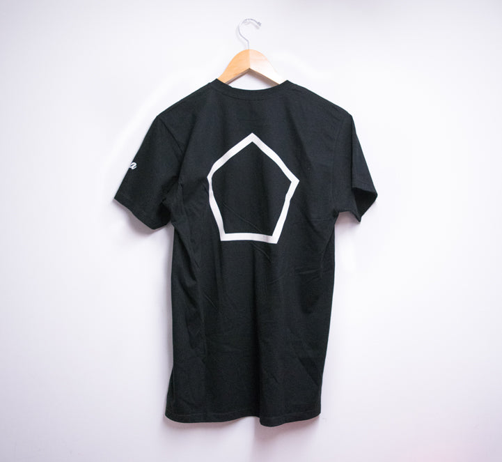 picture of the backside of a black t-shirt with hanger hung against a white wall. T-shirt has a pentagon printed in white