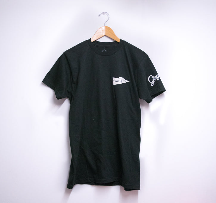 front picture of t-shirt with hanger hung against a white wall. T-shirt has logo printed heart side in white
