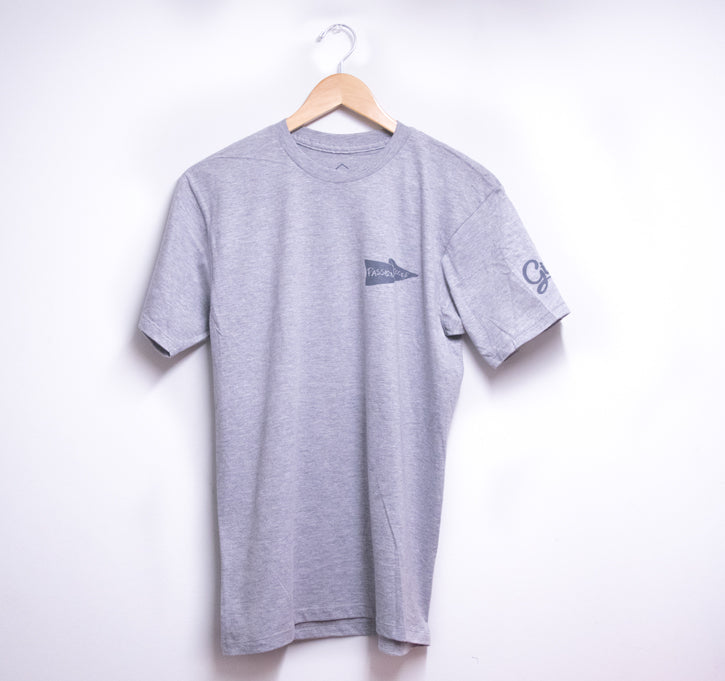 picture of the front side of a grey t-shirt with hanger hung against a white wall. T-shirt has logo printed heart side in black.