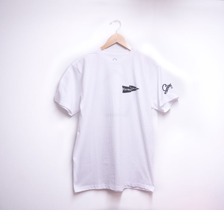 picture of the front side of a white t-shirt with hanger hung against a white wall. T-shirt has logo printed heart side in black.