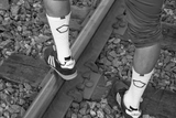 picture of white crew socks of model posing on railroad tracks