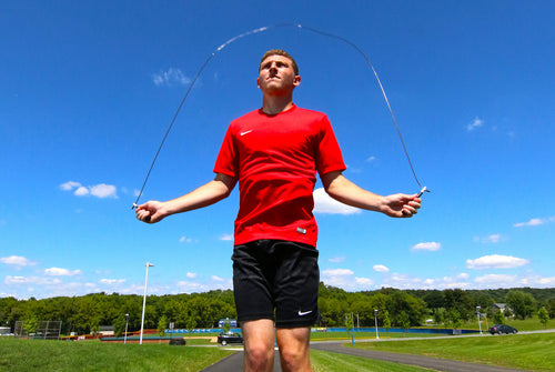 general picture of a male athlete jumping rope during daytime