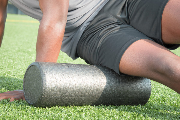 picture of a male african american athlete massaging their musle on a foam roller.
