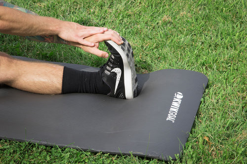 picture of a caucasian male stretching their leg on a black mat. Pictured on a grass field.