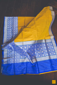 This is a gorgeous Banarasi Silk Saree with yellow body consisting of Tussar silk and the blue border is woven in pure silk with woven kadhwa elephant motifs. The blouse is blue in colour with woven border. New trend of Banarasi Saree designs, Banarasi Saree for artists, art lovers, architects, saree lovers, Saree connoisseurs, musicians, dancers, doctors, Banarasi silk saree, indian saree images, latest sarees with price, only saree images, new Banarasi saree design.