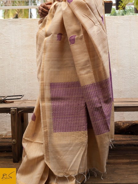 A bright and natural tussar silk saree in combination with a lovely royal shade of purple. The saree has the contrast purple woven buttas which adds to the elegance . This saree has a zari border and zari and silk woven gorgeous pallu.