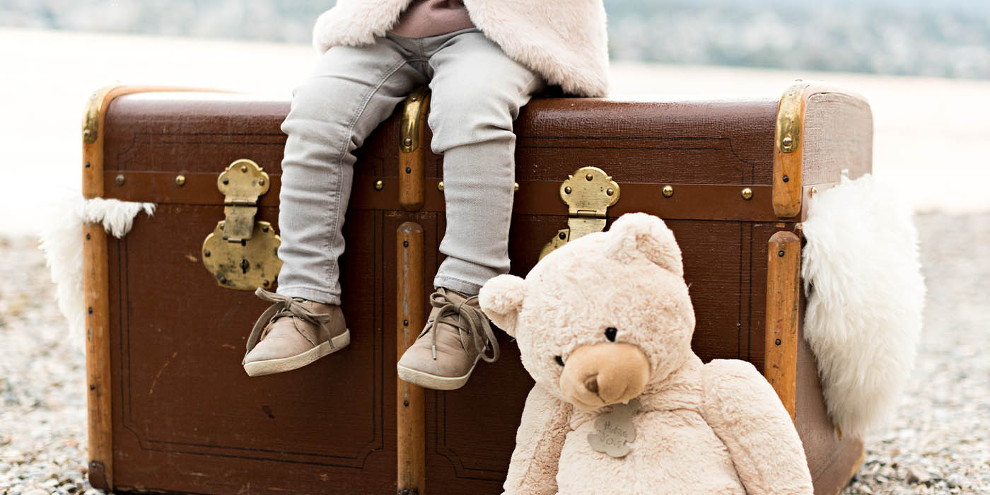 Child sitting on suitcase with teddy bear