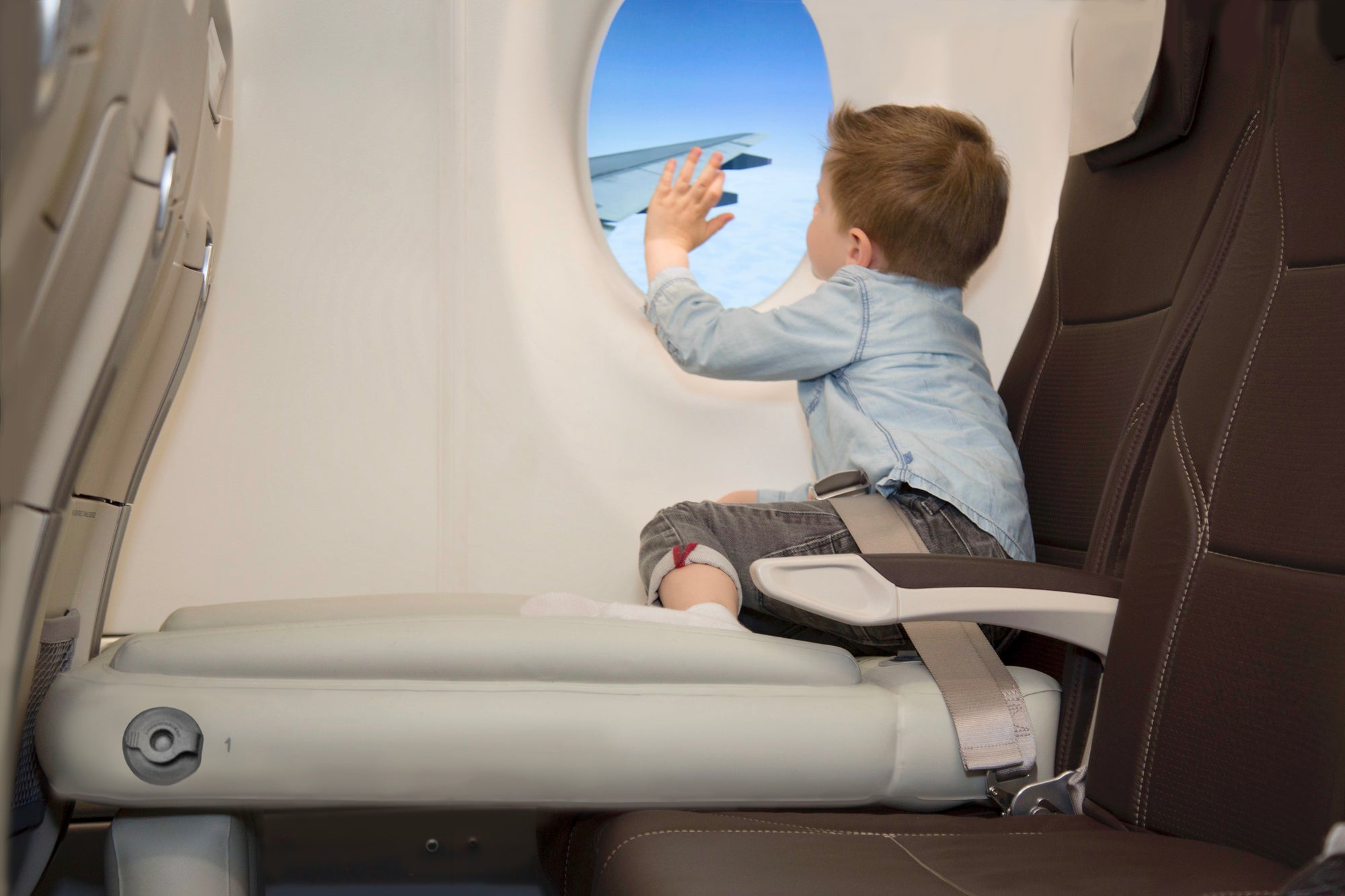 Boy looking out of a plane window and waving