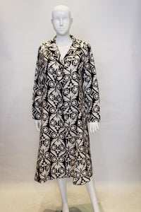 A vintage 1960s black and white graphic print duster coat