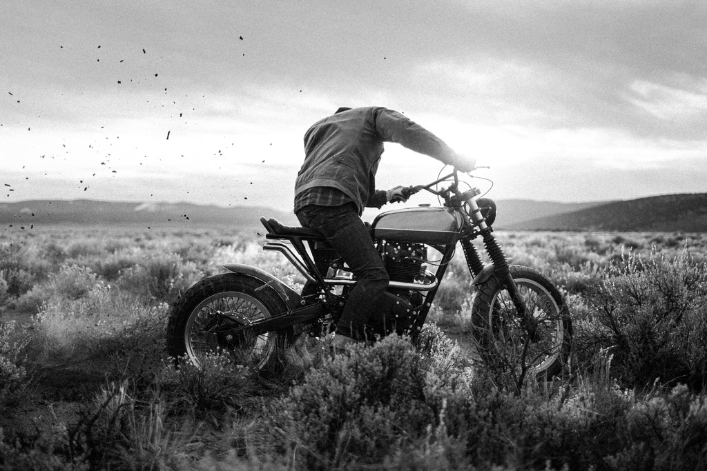 photo of person on a dirt bike twisting the throttle and spinning the back tire kicking up dirt before they drive away