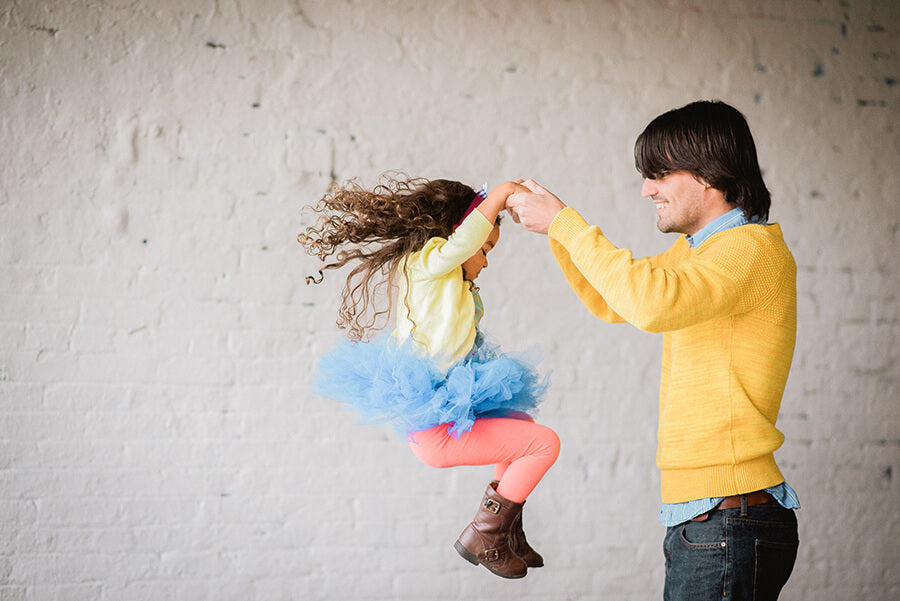 a three year old girl black girl with long curly hair is swung around by her dad in this fun and playful image by latasha haynes photographer