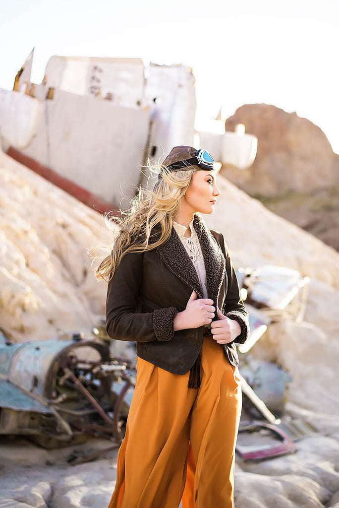 a gorgeous woman with long blonde hair wearing an old aviator helmet and glasses on the top of her head looks off to the side as the wind blows her hair
