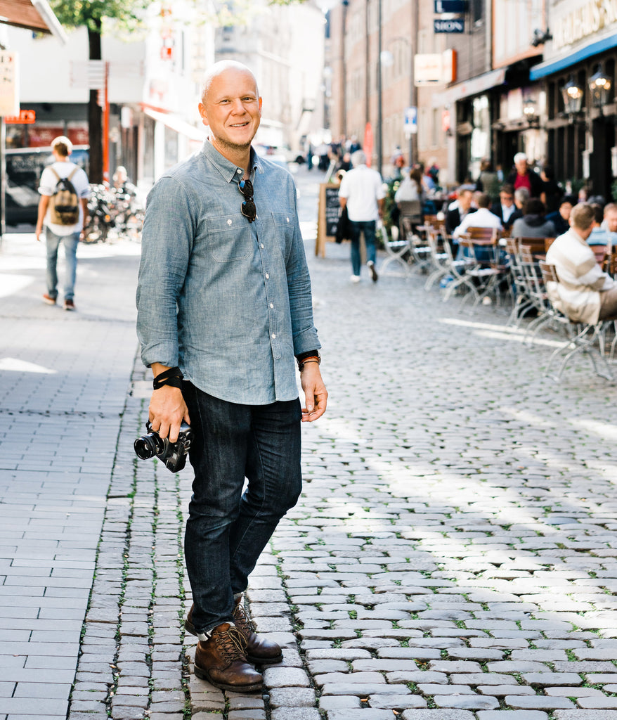 kirk mastin stands in the street in cologne germany with camera in hand smiling in the sunshine