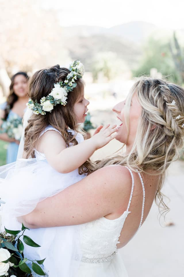 bride on her wedding day holding the flower girl in her arms as they smile looking at one another