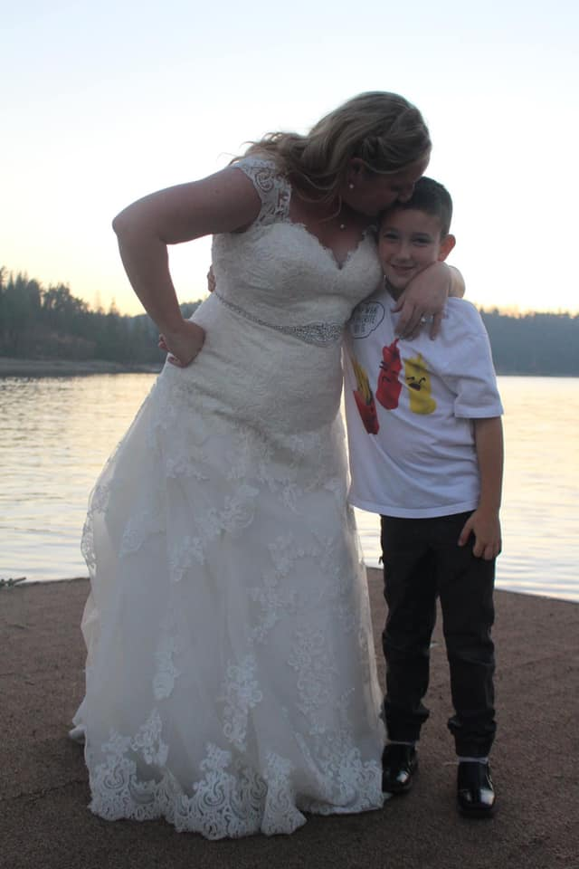 bride in her wedding dress on the beach with her son giving him a kiss on the head