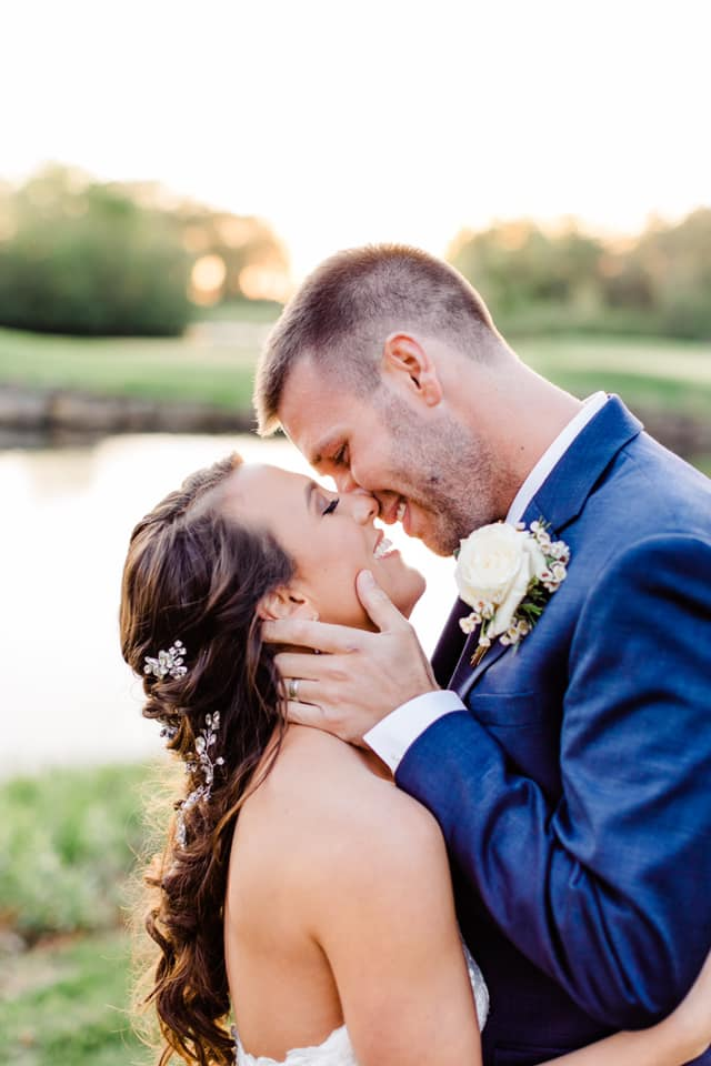 photo of couple from the torso up on their wedding day holding each other close and almost kissing