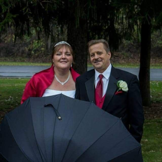 couple stands together in the rain holding an umbrella smiling together on their wedding day