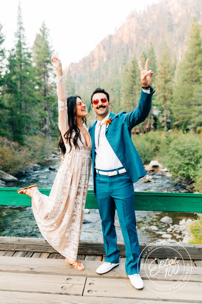 couple on a bridge dressed up giving the peace sign with a watermark