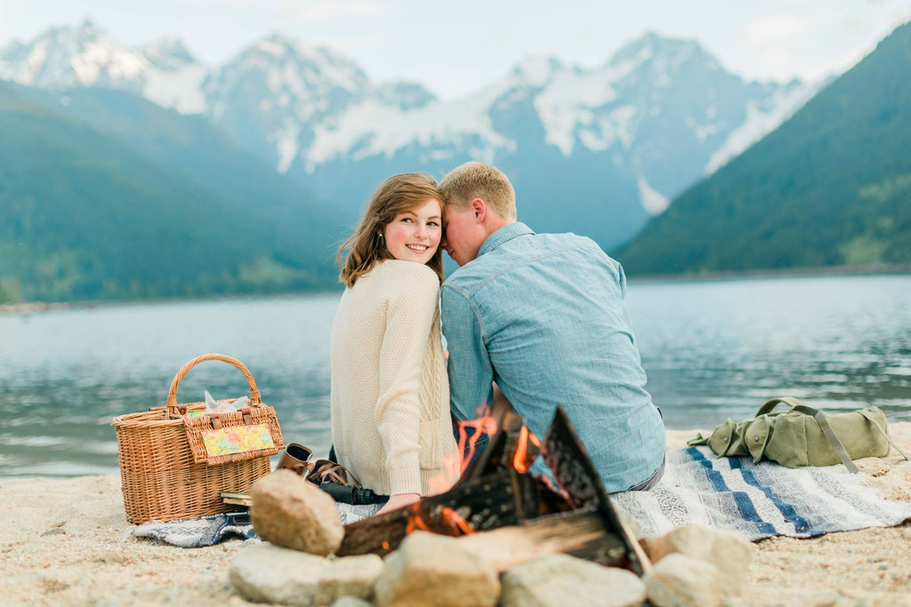 A couple smiles and cuddles while having a picnic in the mountains, image edited with Mastin Labs Fuji Original presets.