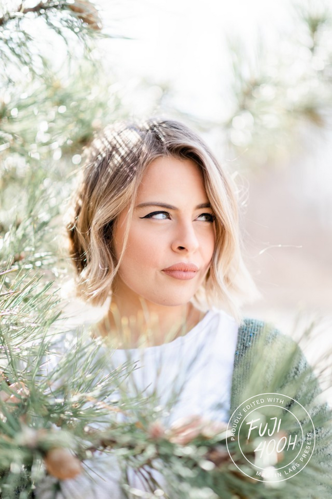 blonde woman standing behind a pine tree looking off with a watermark