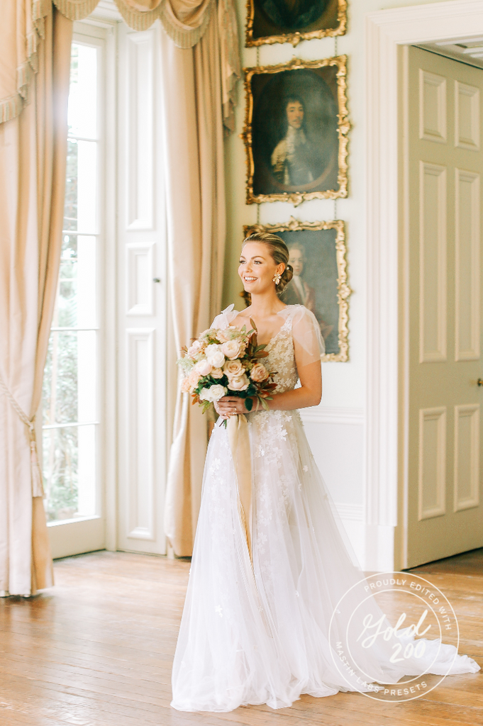 bride smiles standing in her dress with a watermark on the photo
