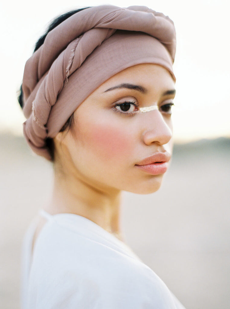 film image by erich mcvey of a gorgeous, delicate-featured, asian woman wearing a turban with beautiful soft pink cheeks and delicate light paint across her nose