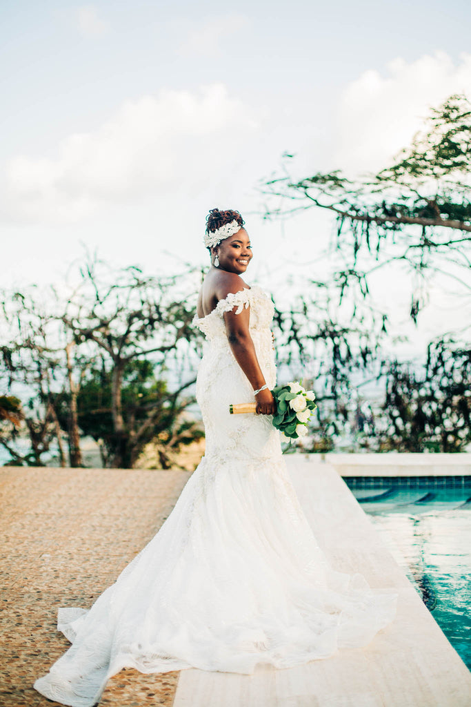 bride stands showing off her beautiful wedding gown by the pool smiling under the sunshine