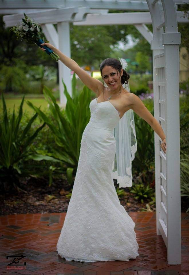 bride stands holding her bouquet raised smiling under a white gazebo