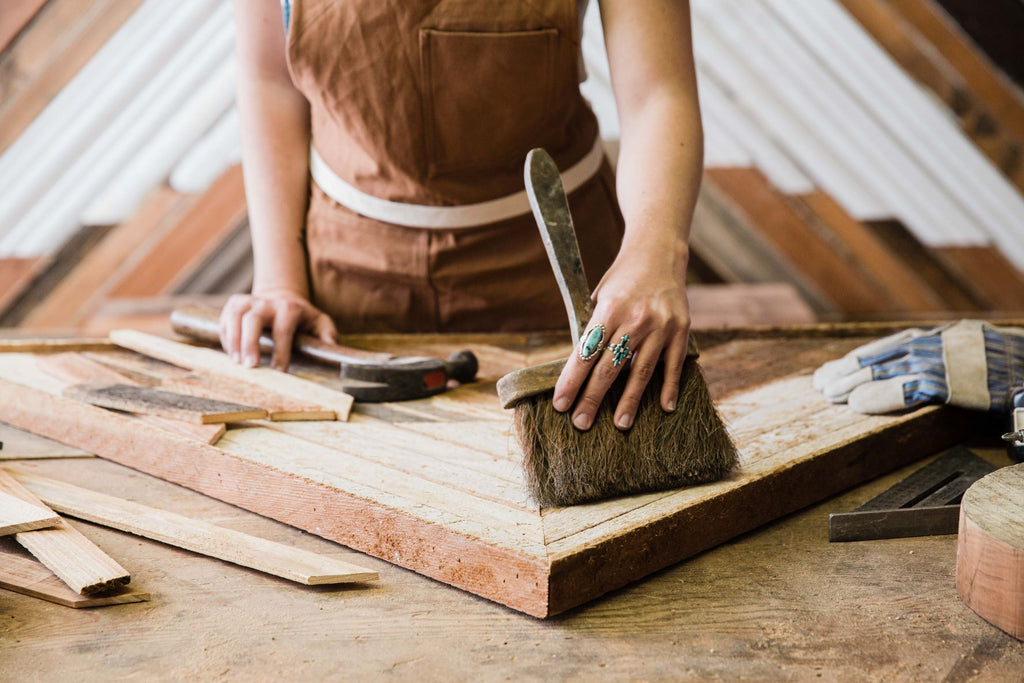 An artisan using a brush on a woodworking craft, image edited with Portra Original Mastin Labs presets.