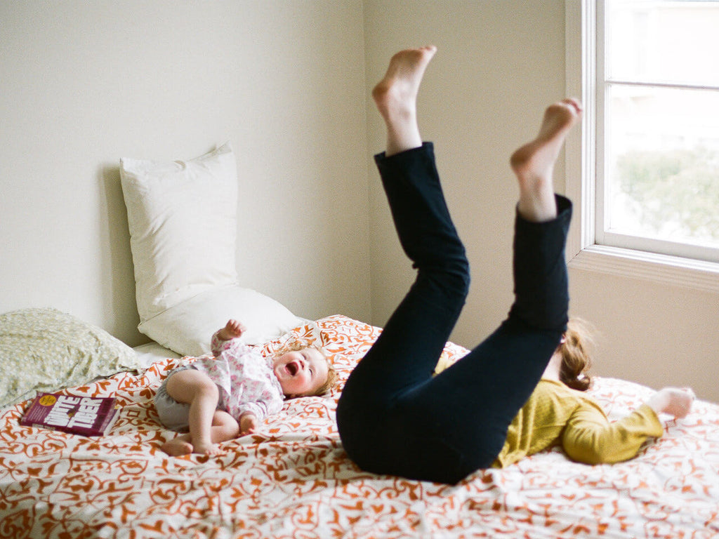a baby lays on a bed beside a book laughing in these tips for photographing your own children with mastin labs