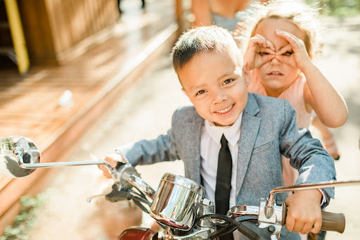 two kids sit on a mini motorcycle together as the young boy in front smiles the little girl behind him creates makeshift glasses with her fingers