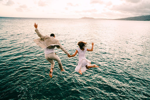 bride and groom jump off a boat into the ocean celebrating all the smart passive income they're making as photographers