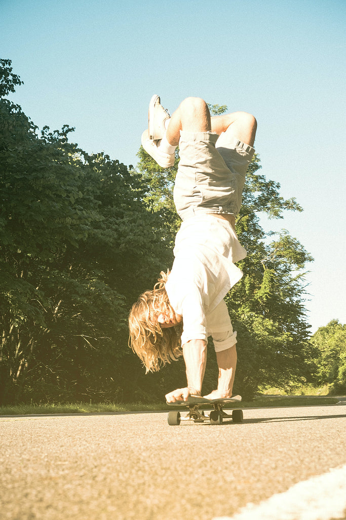 dude with long hair does handstand on a skateboard in the summer sunshine