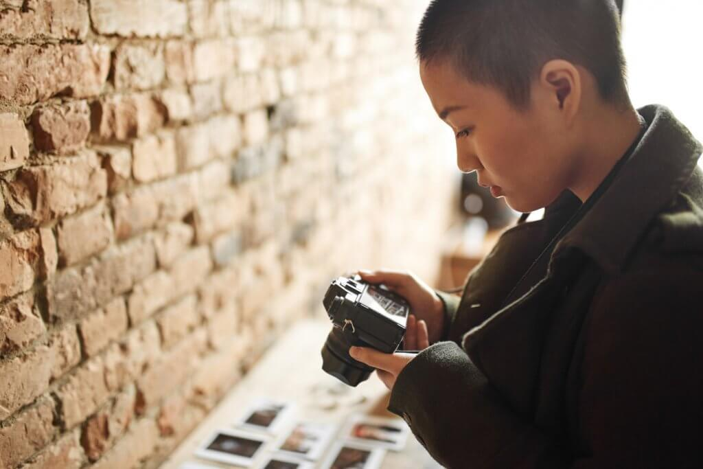 asian woman with close cropped short hair holds a camera and looks down at the lcd screen in this Mastin labs Community blog about finding your confidence as a photographer