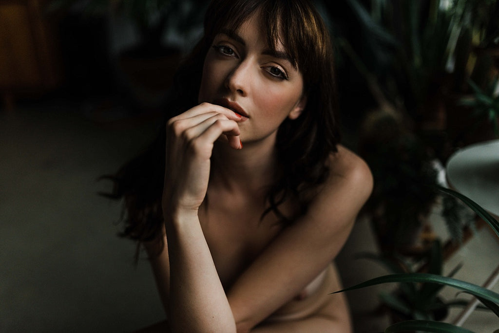 A woman poses for a boudoir photoshoot with Stacey Krolow; edited with Mastin Labs Portra Pushed presets.