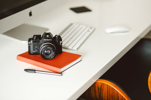 camera sits on a desk on top of an orange book with the lens cover off